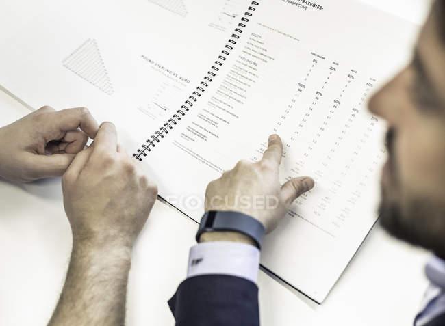 За плечі двох бізнесменів на офісному столі, вказуючи на документи з фінансовим звітом — стокове фото