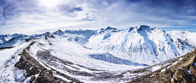 Panoramic view of snow covered mountains under cloudy sky — Stock Photo