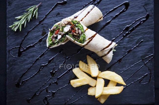 Vue de dessus de tortilla wraps avec puces et garnir de sauce sur ardoise — Photo de stock