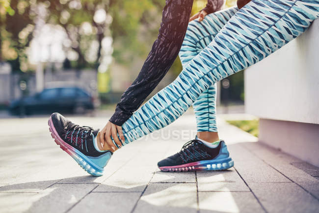 Cropped shot of female runner stretching legs on sidewalk — Stock Photo