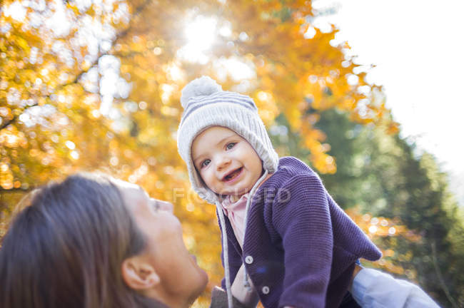 Mother holding up smiling baby girl — Stock Photo