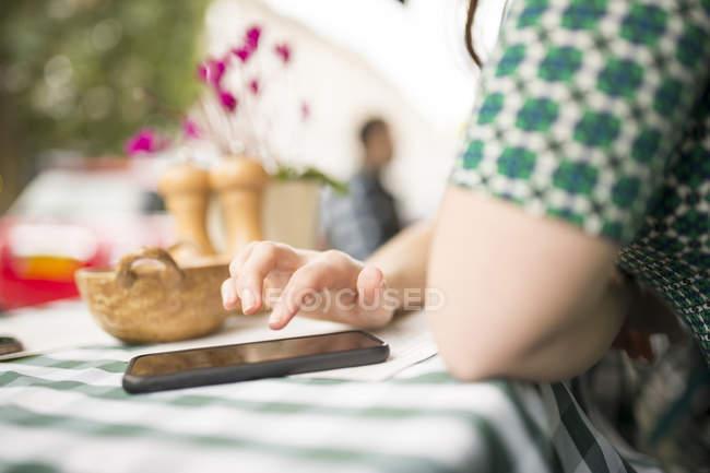 Куповані зору жінки на тротуарі кафе за допомогою смартфона — стокове фото