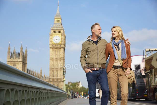 Couple walking on westminster bridge together, London, UK — стокове фото