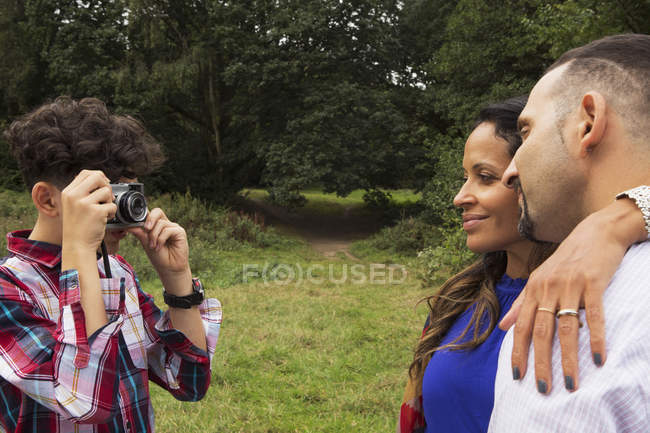 Teenage boy photographing parents outdoors, using camera — Stock Photo