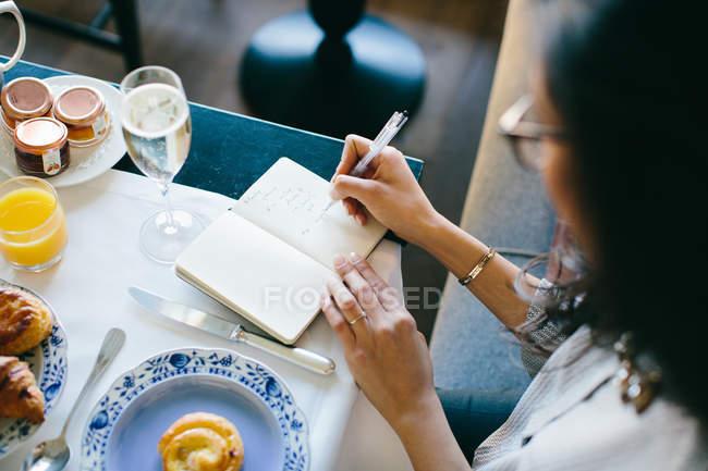 Jovem mulher fazendo anotações enquanto tendo champagne-almoço no hotel boutique em Itália — Fotografia de Stock
