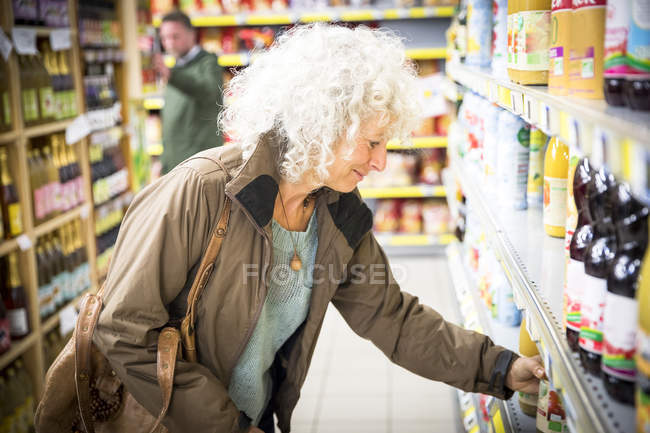 Mature woman in supermarket, taking bottle of juice from shelf — Stock Photo