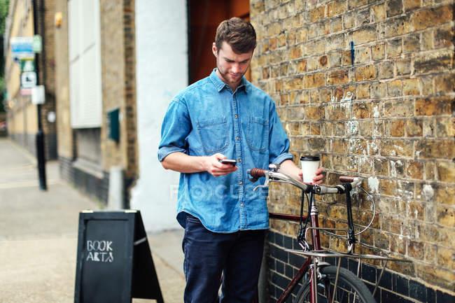 Молодой человек держит кофе и проверяет мобильный телефон, толкая велосипед прислониться к кирпичной стене — стоковое фото