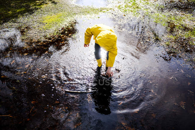 Boy in yellow anorak bending forward in park puddle — Stock Photo