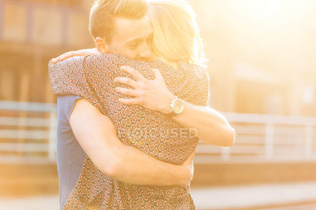 Young couple hugging in sunlight — Stock Photo