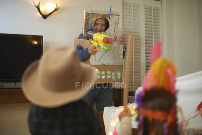 Homem sênior em injetores do brinquedo do tiro do traje do robô com netos vestidos acima — Fotografia de Stock
