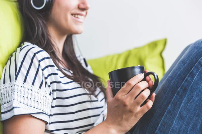 Женщина сидит на диване в наушниках, держа чашку кофе улыбаясь — стоковое фото