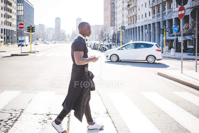 Side view of man crossing road with headphones around neck — Stock Photo