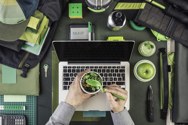 Cropped image of man holding salad whilst preparing hiking equipment and laptop — Stock Photo