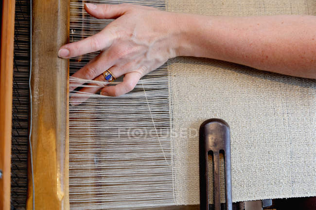 Hands of young woman using loom — Stock Photo