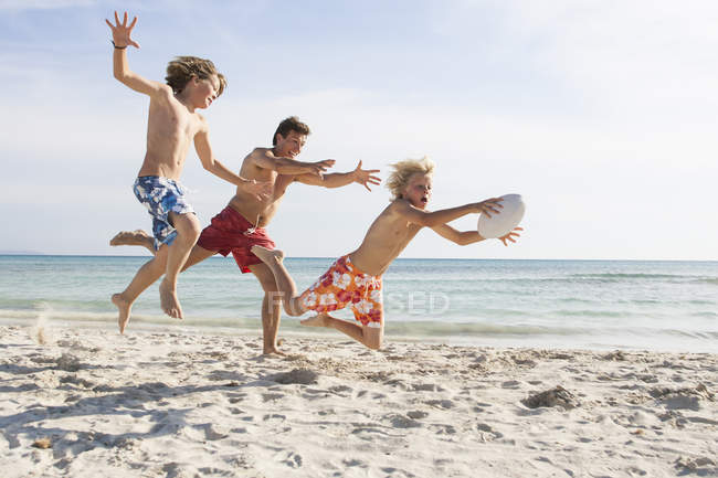 Boy and father chasing brother with rugby ball on beach, Majorca, Spain — Stock Photo