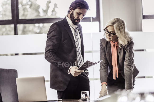 Businesswoman and businessman reading paperwork in office — Stock Photo