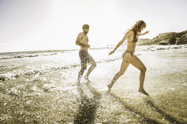 Casal adulto médio usando biquíni e shorts de natação salpicando no mar, Cape Town, África do Sul — Fotografia de Stock