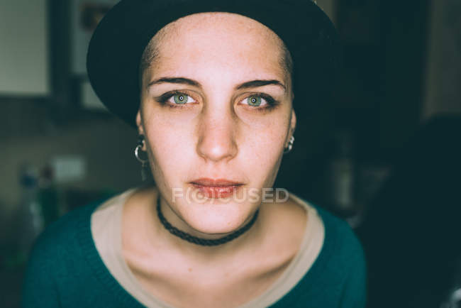 Head and shoulder portrait of blue eyed young woman in trilby — Stock Photo