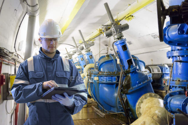 Worker using digital tablet to take readings in straining gallery in hydroelectric power station — Stock Photo