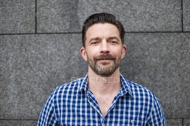 Head and shoulder portrait of mature man in font of wall — Stock Photo