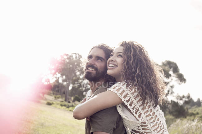 Young woman with arms around young man looking up smiling — Stock Photo