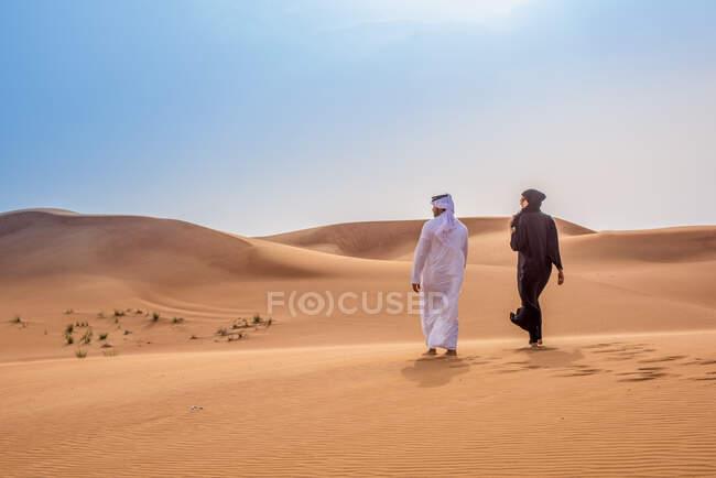 Пара одягнена в традиційний одяг середнього сходу, який ходить по пустелі, Дубай, Об