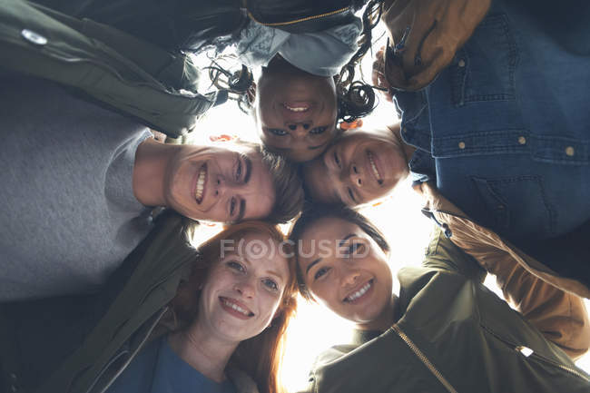 Low angle portrait of female and male college students with arms around each other — Stock Photo