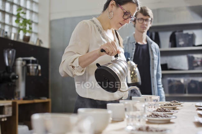 Coffee taster pouring hot water into cup of coffee — Stock Photo