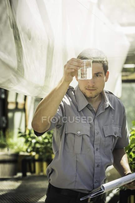 Wissenschaftler betrachten Flüssigkeit in Pflanze Wachstum Forschung Einrichtung Gewächshaus — Stockfoto