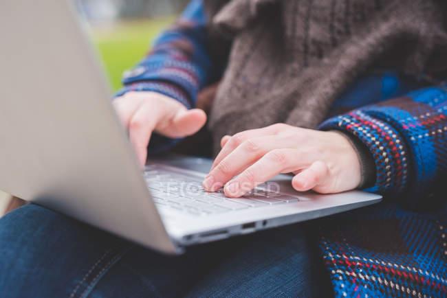 Молода жінка, використовуючи ноутбук, на відкритому повітрі, Закри — стокове фото