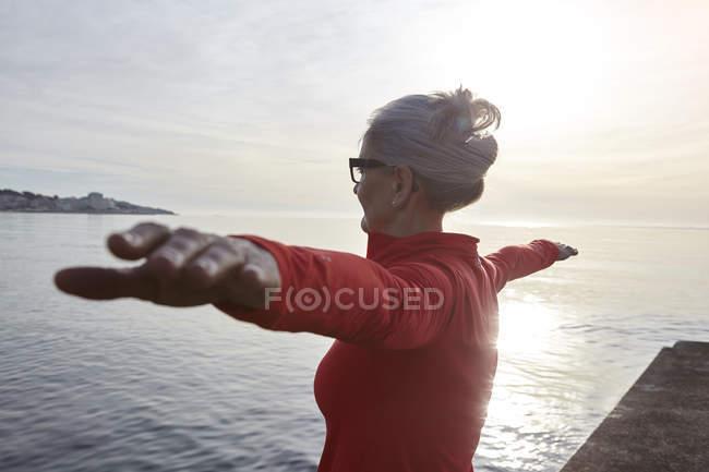 Femme d'âge mûr se trouvant à côté de l'eau, en position d'yoga, vue arrière — Photo de stock