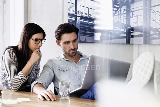 Colleghi in carica utilizzando computer portatile insieme — Foto stock