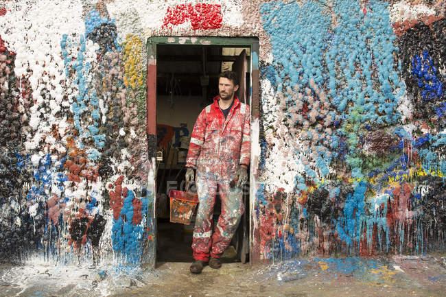 Художник-мужчина, прислонившийся к разбрызганным краской дверям — стоковое фото