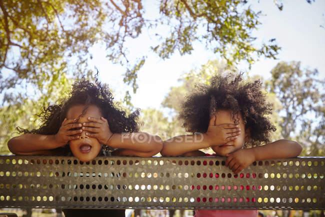 Retrato de duas irmãs novas que inclinam-se de encontro à cerca, cobrindo os olhos — Fotografia de Stock