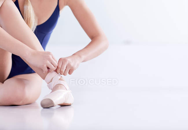 Cropped shot of female ballet dancer sitting on dance studio floor tying ballet slipper — Stock Photo