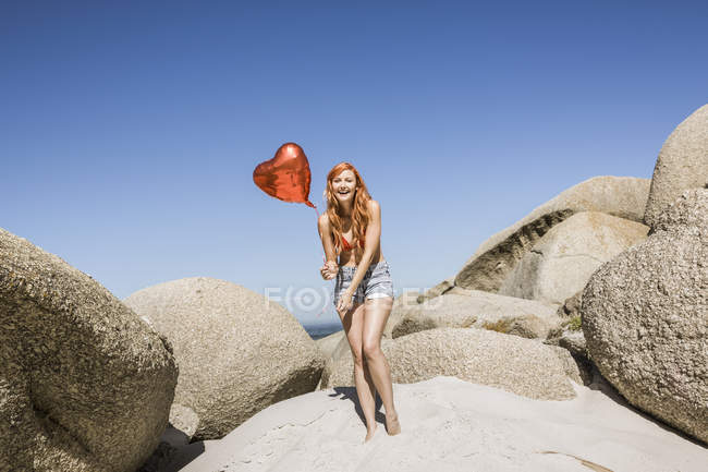 Young woman on beach, holding heart shaped balloon — Stock Photo
