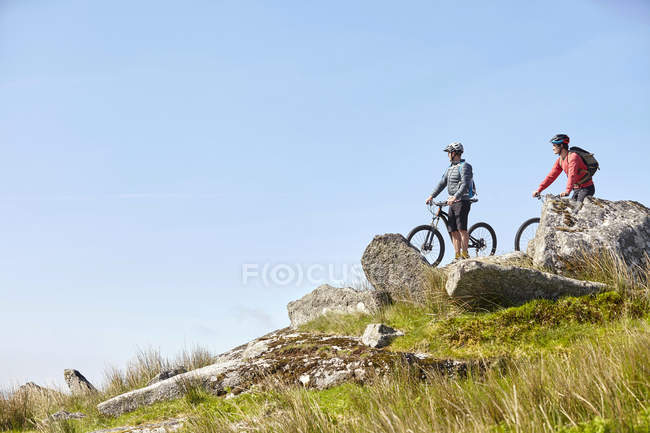 Cyclists on bicycles on rocky outcrop looking away — Stock Photo