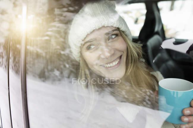 Женщина пьет кофе в машине — стоковое фото