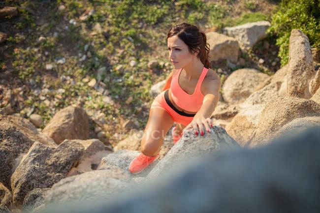 Mujer joven haciendo ejercicio al aire libre, escalada de rocas, elevado ver - foto de stock
