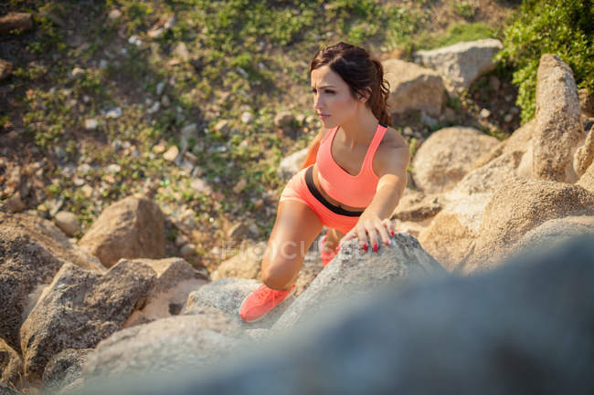 Young woman exercising outdoors, climbing rocks, elevated view — Stock Photo