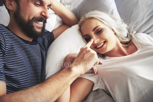 Couple lying in bed, fooling around, man poking female nose — Stock Photo