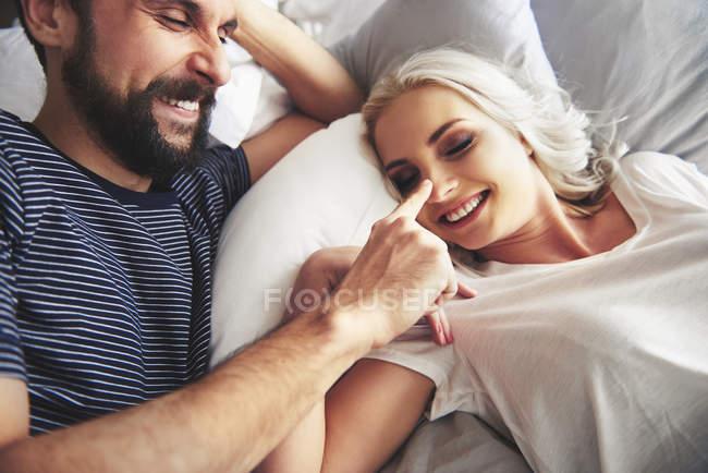 Coppia sdraiato nel letto, scherzare, uomo frugando naso femmina — Foto stock