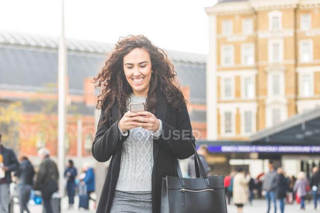 Metà donna adulta, camminare all'aperto, utilizzando smartphone, sorridente — Foto stock