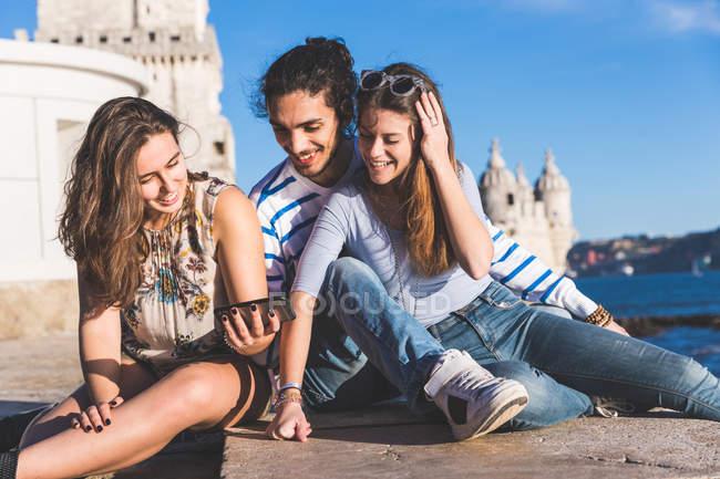 Três amigos, sentados na parede por mar, Torre de Belém ao fundo, Lisboa, Portugal — Fotografia de Stock