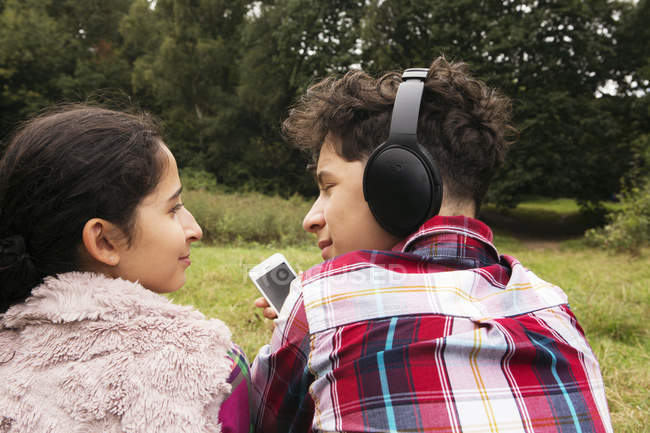 Brother and sister, sitting outdoors, listening to music, rear view — Stock Photo