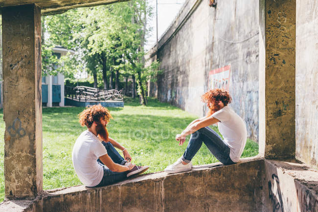 Young male hipster twins with red beards sitting on wall — Stock Photo