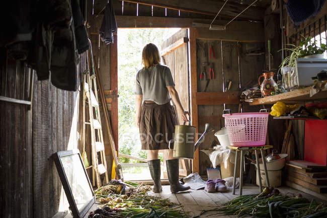 Молоді жінки, що несе лійка виглядає зі садовий сарай — стокове фото