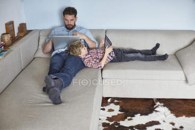 Niño acostado en el sofá con el padre utilizando la tecnología - foto de stock