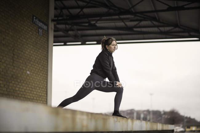 Femelle coureur penché vers l'avant qui s'étend sur la plateforme d'entrepôt — Photo de stock