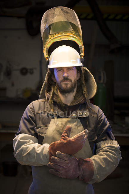 Portrait of mid adult male foundry worker putting on protective gloves in bronze foundry — Stock Photo